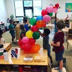 Children making a bridge out of balloons, a STEAM activity.
